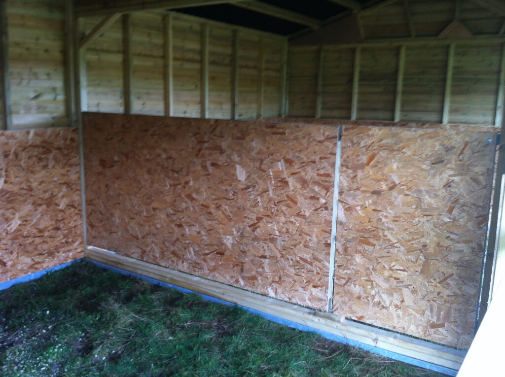Internal shot of field shelter, lined with os board with a partition.