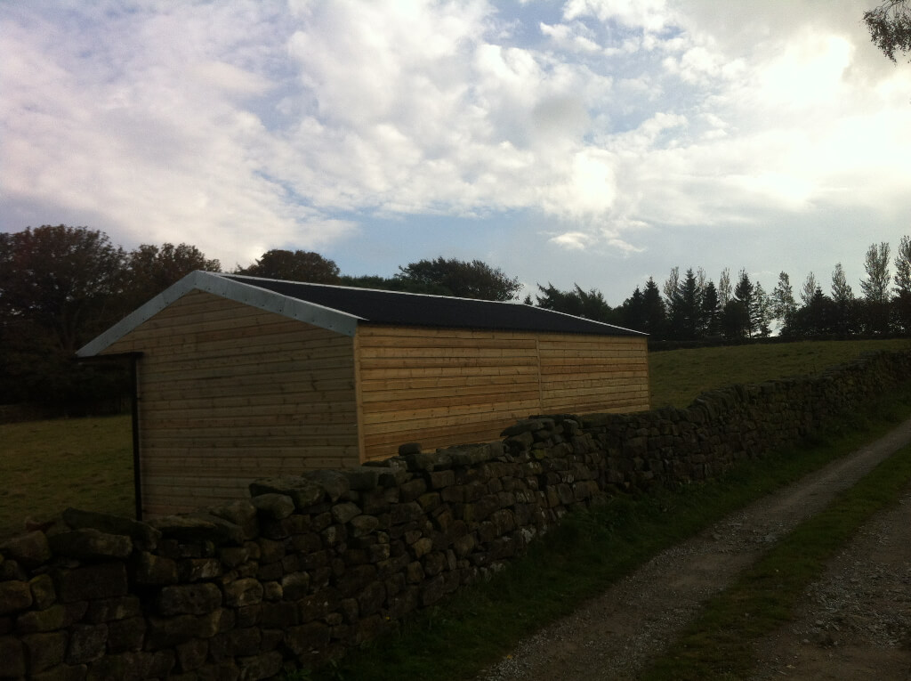 Field shelter clad in ship lap boards with guttering