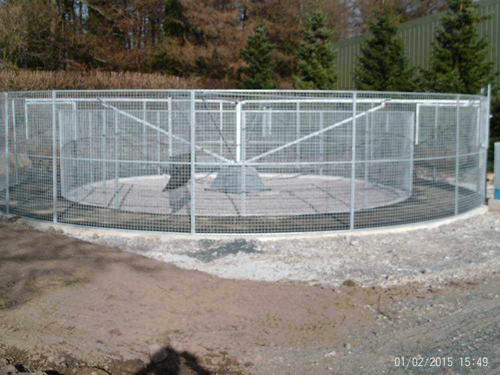 36' diameter horse walker with mesh fencing and rubber paving installed in a new livery yard near Lancaster.