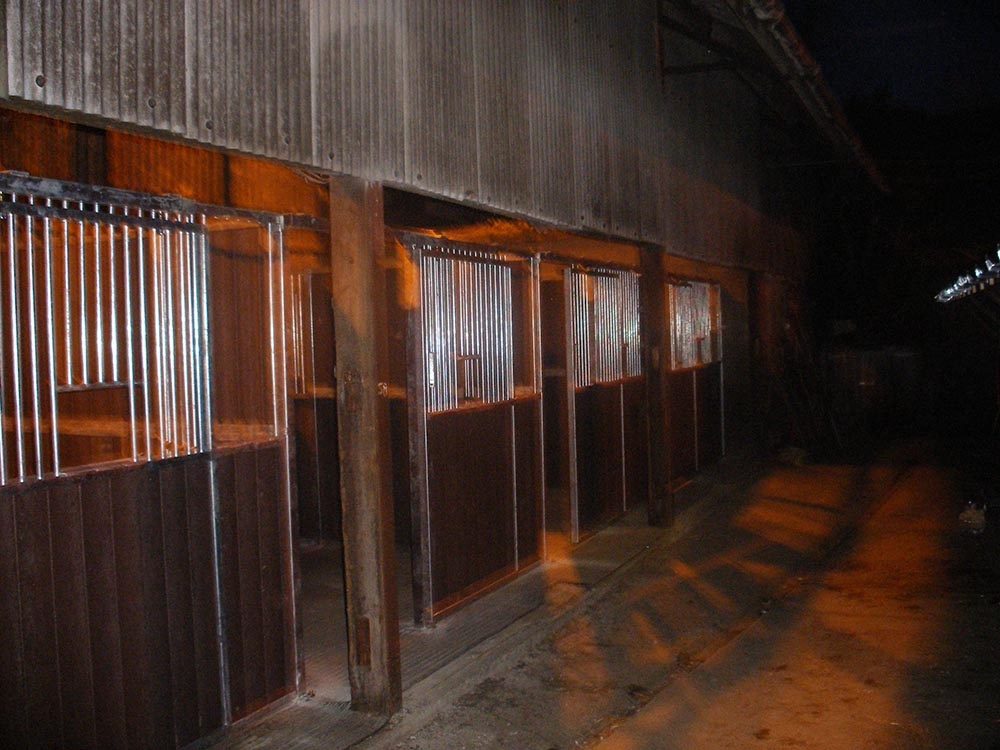 Internal stables at night with sliding doors at Eventing yard in North Yorkshire